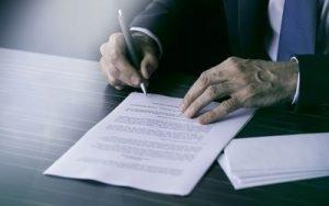 businessman-signing-document-598314159-589874bf3df78caebc2e1de5-300×188